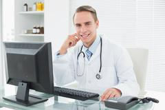 Confident doctor sitting with computer at medical office - stock photo