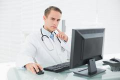 Serious doctor using computer at medical office Stock Photos