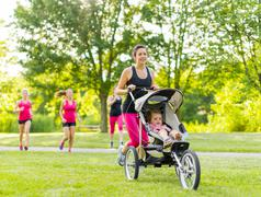 Active mother keeping fit by jogging Stock Photos