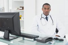 Serious male doctor with computer at medical office Stock Photos