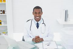 Smiling doctor with laptop at medical office Stock Photos