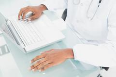 Hands using laptop at medical office - stock photo