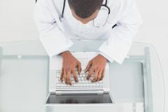 Overhead view of a male doctor using laptop Stock Photos