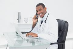 Smiling doctor using phone and laptop at medical office Stock Photos