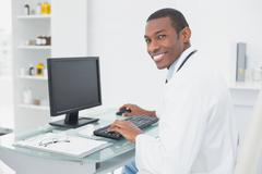 Smiling doctor using computer at medical office Stock Photos
