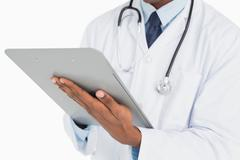 Stock Photo of Close up mid section of a male doctor writing on clipboard