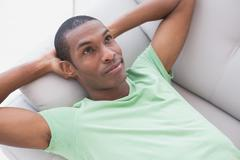 Thoughtful relaxed young Afro man lying on sofa - stock photo