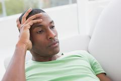 Stock Photo of Thoughtful relaxed young Afro man lying on sofa