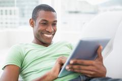 Stock Photo of Casual smiling Afro man using digital tablet on sofa