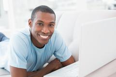Smiling Afro man with laptop lying on sofa Stock Photos