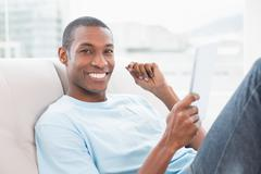 Casual smiling Afro man using digital tablet on sofa - stock photo