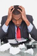 Frustrated Afro businessman with head in hands at desk Stock Photos