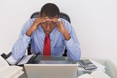 Afro businessman with head in hands at desk - stock photo