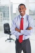 Elegant smiling Afro businessman standing in office Stock Photos
