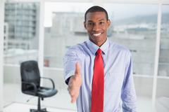 Stock Photo of Elegant smiling Afro businessman offering handshake at office