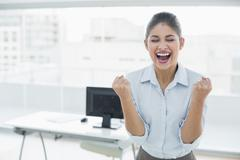 Happy businesswoman clenching fists in office Stock Photos