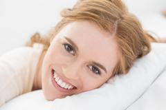 Close up of pretty young woman resting in bed - stock photo