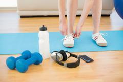 Female tying shoes with sporty equipment in fitness center - stock photo