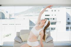 Sporty female stretching hand in fitness center - stock photo