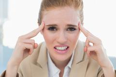 Close up of businesswoman suffering from headache - stock photo