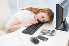 Asleep businesswoman yawning on keyboard at office - stock photo