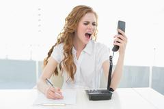 Businesswoman shouting into the phone at office - stock photo