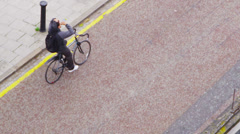 Young man in hooded sweatshirt cycling through an urban area Stock Footage