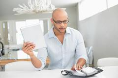 Casual man with digital tablet and diary at home Stock Photos