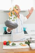 Man tossing vegetables in air at kitchen Stock Photos