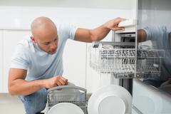 Serious man using dish washer in kitchen - stock photo