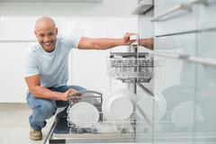 Portrait of smiling man using dish washer in kitchen - stock photo