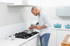 Side view of man preparing food in kitchen - stock photo