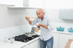 Man tasting food while preparing in kitchen - stock photo