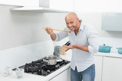 Man tasting food while preparing in kitchen Stock Photos