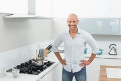 Portrait of smiling young man besides kitchen stove - stock photo