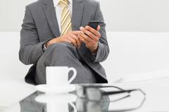 Mid section of an elegant businessman text messaging - stock photo