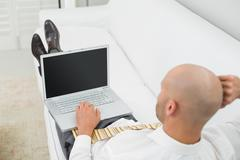 Bald businessman using laptop on sofa at home - stock photo