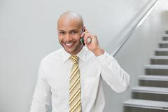 Stock Photo of Smiling businessman using cellphone against staircase