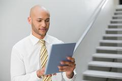 Serious elegant young businessman using digital tablet - stock photo
