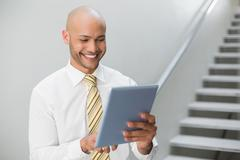 Stock Photo of Smiling elegant young businessman using digital tablet