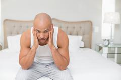 Portrait of bald man suffering from headache in bed - stock photo