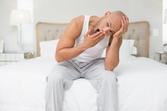 Bald man sitting and yawning in bed - stock photo