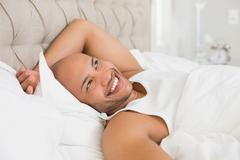 Smiling young bald man resting in bed - stock photo