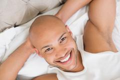 Close up of a smiling young bald man resting in bed - stock photo