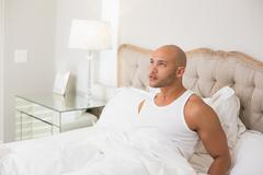 Thoughtful young bald man sitting in bed - stock photo