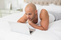 Casual bald man using laptop in bed - stock photo