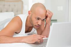 Serious casual bald young man using laptop in bed Stock Photos