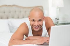 Stock Photo of Smiling casual bald young man using laptop in bed
