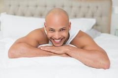 Smiling casual bald young man lying in bed - stock photo