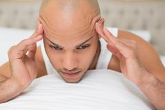 Bald man suffering from headache in bed - stock photo
